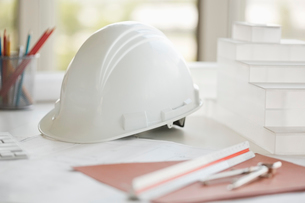 Hardhat and architectural model on deskの写真素材 [FYI02294273]