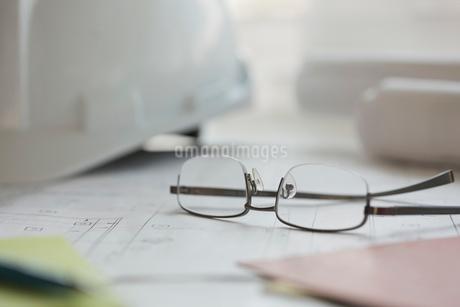 Eyeglasses and blueprint on office deskの写真素材 [FYI02294303]