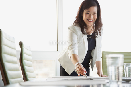 Portrait of businesswoman reviewing blueprint at conference tableの写真素材 [FYI02294304]