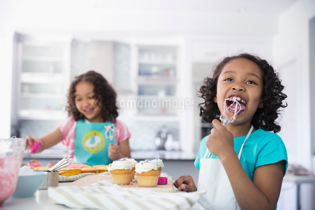 Little girl licking icing off whisk while decorating cupcakesの写真素材 [FYI02294305]