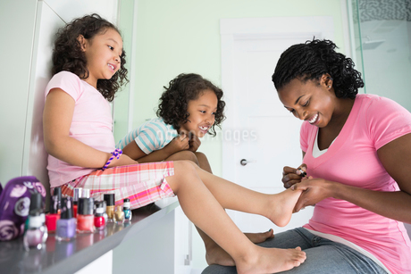 Mother painting young daughter's toenailsの写真素材 [FYI02294361]