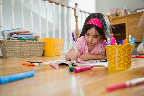 Little girl coloring in book while lying on floorの写真素材 [FYI02294392]