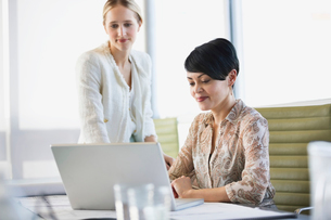 Businesswomen sharing laptop in officeの写真素材 [FYI02294402]
