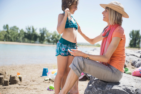 Grandmother applying sunscreen to little girl on beachの写真素材 [FYI02294421]