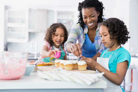 Mother and daughters adding sprinkles to cupcakesの写真素材 [FYI02294503]