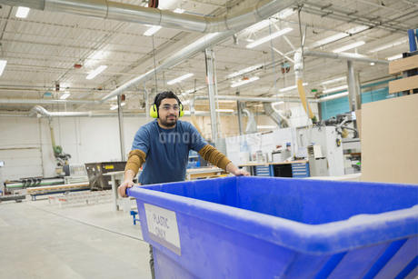 Worker pushing plastic bin in warehouseの写真素材 [FYI02294517]