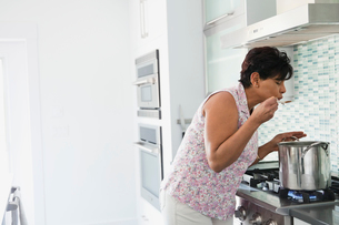 Woman tasting food while cooking in domestic kitchenの写真素材 [FYI02294564]