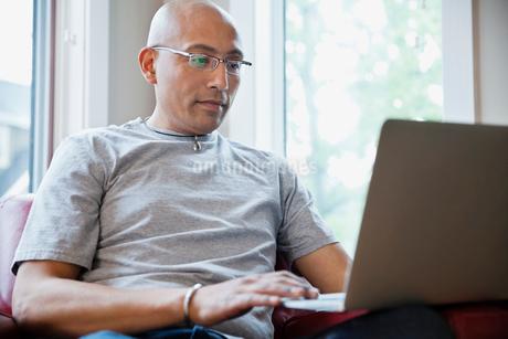 Mature man browsing on laptop at homeの写真素材 [FYI02294588]