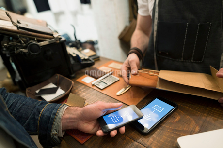Customer using contactless payment in leather shopの写真素材 [FYI02294662]