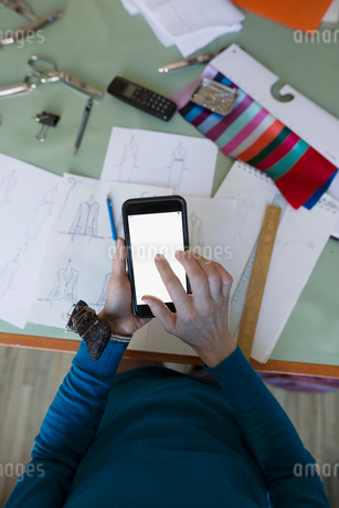 Dressmaker using cell phone at workbenchの写真素材 [FYI02294726]