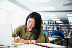 College student with headphones researching at laptop in libraryの写真素材 [FYI02294779]