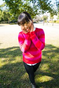 ピンク色のセーターを着て両手を頬に当て笑う女性の写真素材 [FYI02294851]