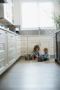 Brother and sister playing with pots and pans on kitchen floorの写真素材 [FYI02294968]