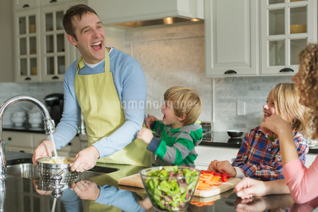 Happy father rinsing spaghetti at sink while family watches.の写真素材 [FYI02294986]