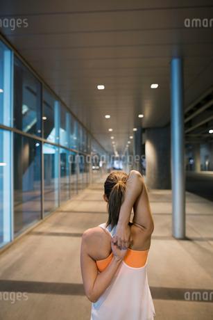 Runner stretching arms on city sidewalkの写真素材 [FYI02294999]