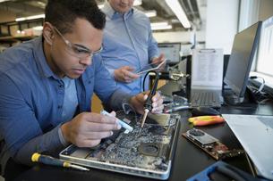 Engineers assembling laptop electronicsの写真素材 [FYI02295005]