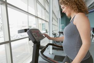 Profile of pretty, pregnant woman at fitness center.の写真素材 [FYI02295008]
