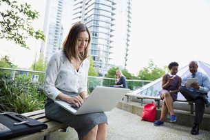 Businesswoman using laptop on bench in cityの写真素材 [FYI02295100]