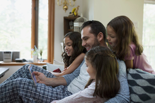 Father and daughters watching video on digital tablet on living room sofaの写真素材 [FYI02295364]