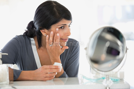 Beautiful mature woman applying cream on face at dressing tableの写真素材 [FYI02295366]