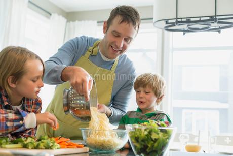 Father putting spaghetti into bowl as sons watch.の写真素材 [FYI02295415]
