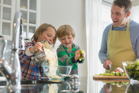 Father watching as son pours spaghetti into bowl.の写真素材 [FYI02295457]
