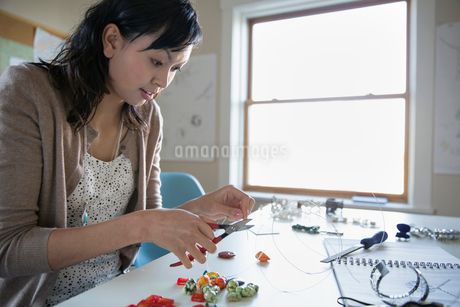 Beautiful woman cutting wire while making jewelry at deskの写真素材 [FYI02295477]