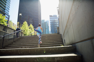 Woman with yoga mat ascending city stepsの写真素材 [FYI02295573]