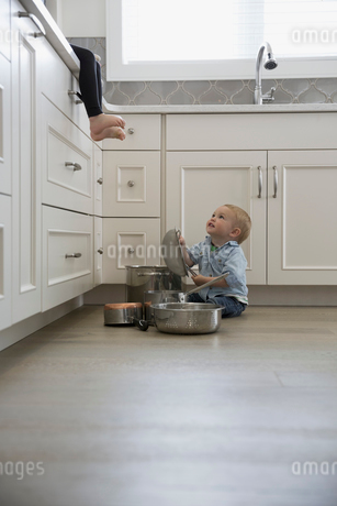 Baby boy playing with pots and pans on kitchen floorの写真素材 [FYI02295583]