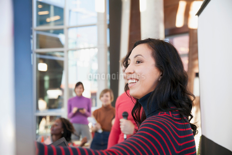 Woman smiling at business presentation with coworkers.の写真素材 [FYI02295592]