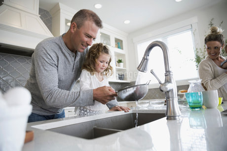 Father and daughter washing berries in kitchen sinkの写真素材 [FYI02295653]