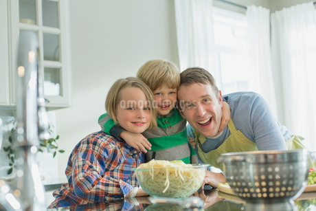 Portrait of dad and sons hugging in kitchen.の写真素材 [FYI02295709]
