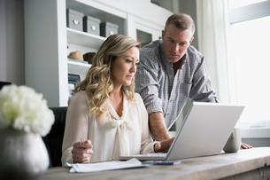 Couple working at laptop in home officeの写真素材 [FYI02295745]