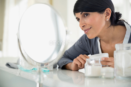 Beautiful woman holding cream bottle while looking in mirror at dressing tableの写真素材 [FYI02295755]