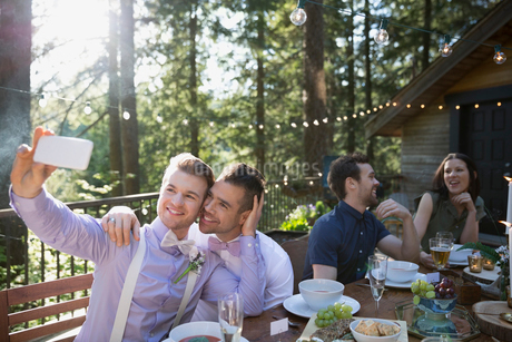 Homosexual couple taking selfie at wedding receptionの写真素材 [FYI02295907]