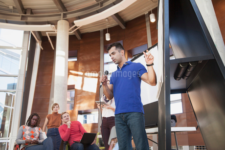 Man with microphone pitching ideas at group.の写真素材 [FYI02295983]