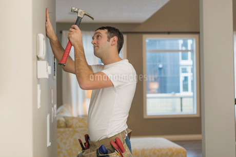 Mid adult man about to hammer nail into wall.の写真素材 [FYI02296025]