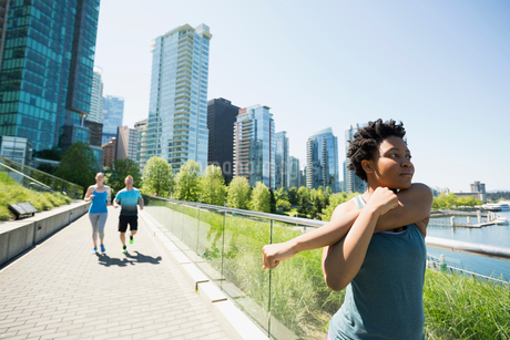 Runner stretching arms at sunny city waterfrontの写真素材 [FYI02296068]