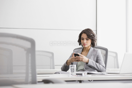 Businesswoman using cell phone in conference roomの写真素材 [FYI02296147]