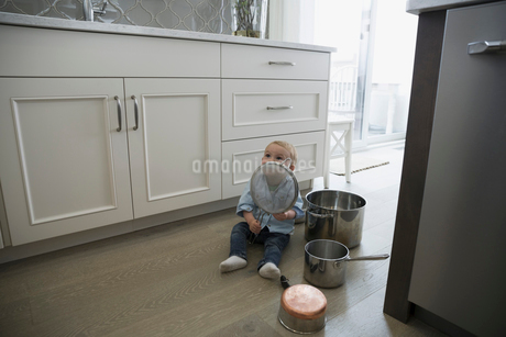 Baby boy playing with pots and pans on kitchen floorの写真素材 [FYI02296572]