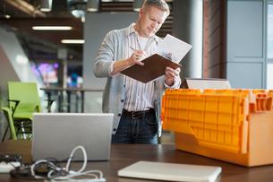 Man checking off list as he unpacks computer hardware.の写真素材 [FYI02296596]