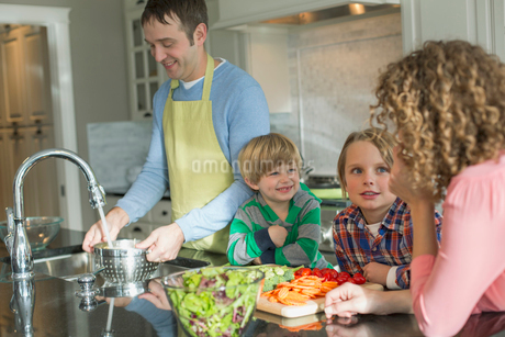 Family of four in kitchen as father prepares dinner.の写真素材 [FYI02296801]
