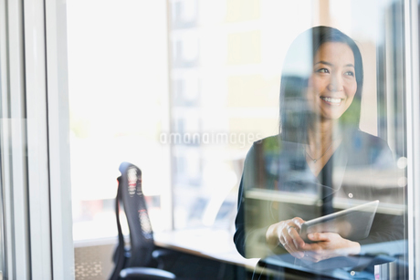 Smiling businesswoman with digital tablet in officeの写真素材 [FYI02296913]