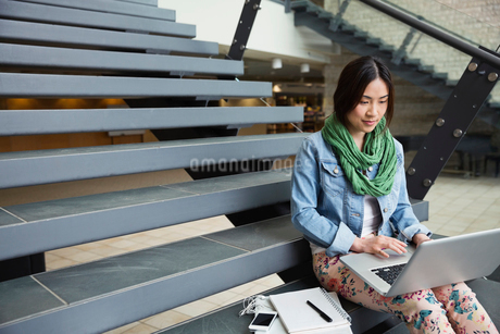Female student using laptop while sitting on steps at college campusの写真素材 [FYI02297044]