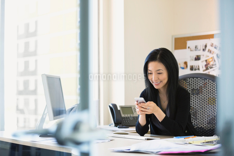 Businesswoman text messaging at desk in officeの写真素材 [FYI02297092]