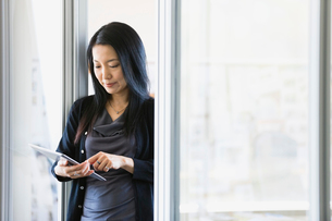 Businesswoman using digital tablet in officeの写真素材 [FYI02297121]