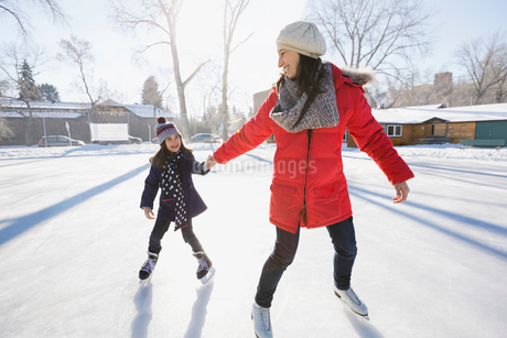 Mother and daughter ice-skating on rinkの写真素材 [FYI02297185]