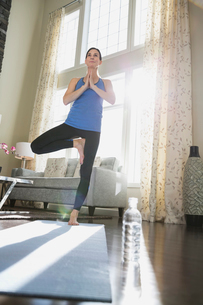 Mature woman performing tree pose at homeの写真素材 [FYI02297385]