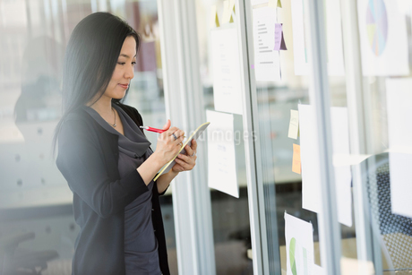 Businesswoman writing on notepad in officeの写真素材 [FYI02297533]