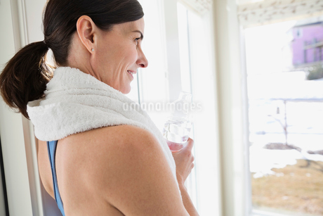 Side view of fit mature woman holding water bottle while through windowの写真素材 [FYI02297535]